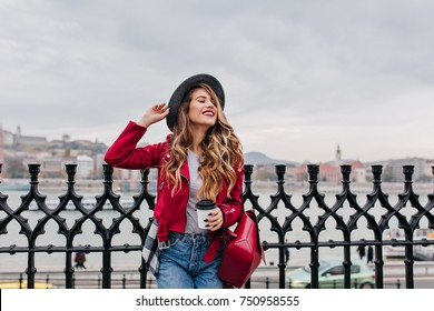 Good-looking girl in jeans and elegant hat posing under gray sky on embankment. Outdoor photo of cute young woman with black manicure drinks coffee on bridge in european city.