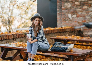 Good-looking girl in short denim pants sitting on wooden table in autumn park. Cute white female model in elegant hat spending time outdoor, drinking coffee in october day.