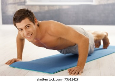 Goodlooking guy doing push up in gym, workout on polyfoam mattress, smiling at camera.?