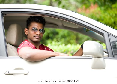 A good-looking Indian man in sunglasses sitting in drivers seat of car outside