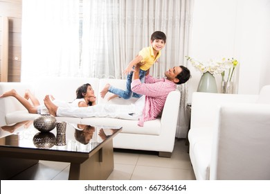 Goodlooking Indian/Asian Playful Father and kids having good time at home while sitting over sofa
