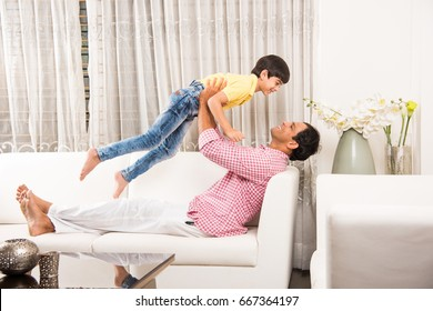 Goodlooking Indian/Asian Playful Father son having good time at home while sitting over sofa