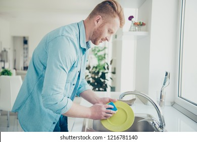 Good-looking man in blue shirt casual stylish trendy wear washing green dishes carefully and attentively stand inside bright flat