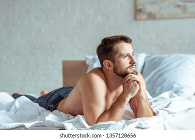 good-looking and muscular man lying on bed and looking away in bedroom