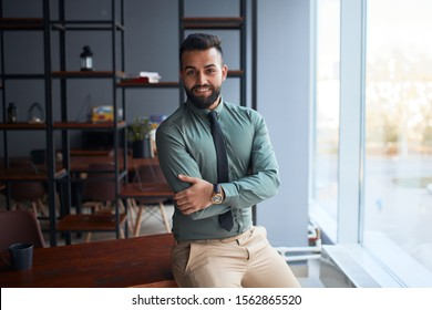 Good-looking personable young man from middle east, businessman standing in office, looking at camera, successful team leader wearing formal wear, posing for photo at workplace next to window