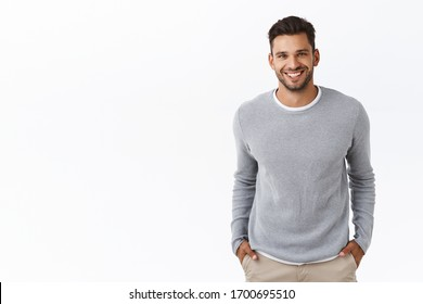 Good-looking stylish modern hispanic guy with stylish haircut, beard, wear grey sweater over t-shirt, hold hands in pockets and smiling joyfully, laughing chatting with friends, white background