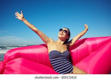 A good-looking woman spending her free time on the hot sunny beach, soaking up the glorious atmosphere of the cloudless sky and a bit waving sea.