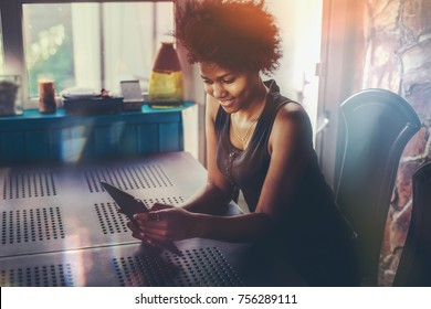 Good-looking young curly Brazilian female with tablet pc in dark room on verandah of house; teenage black female is taking selfie using camera of her digital tablet while sitting at the table