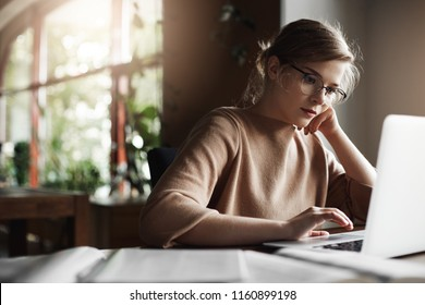 Good-looking young female freelancer tutor sitting in cozy cafe, leaning on hand while checking schedule via laptop, gazing at screen with focused expression, working, preparing material, making notes
