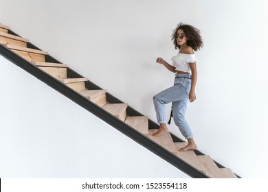 Good-looking young female going upstairs to her room