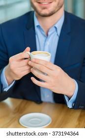 Good-looking young man holding coffee mug.
