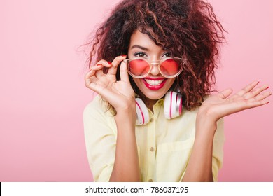 Good-looking young woman with brown skin holding pink sunglasses and posing with surprised smile. Indoor portrait of emotional african female model in elegant yellow attire.