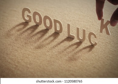 GOODLUCK wood word on compressed or corkboard with human's finger at K letter.
