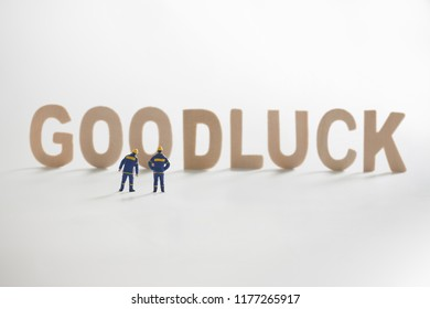 GOODLUCK word  with Miniature people: Engineer standing infront use as business concept.