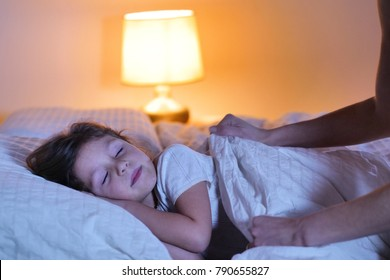 Goodnight mother to her little daughter who sleeps at night in her bedroom and sees the moonlight coming through the window and lighting her sweet face. Concept of: peaceful dreams, family, relaxation