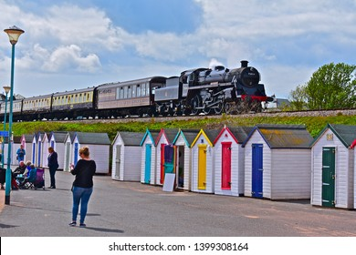 Goodrington, Devon / Engalnd - 5/6/2019:Engine No.75014 'Braveheart' of the Dartmouth Steam Railway, steams into Goodrington station, past a row of colourful beach huts.Pullman Observation Car behind.