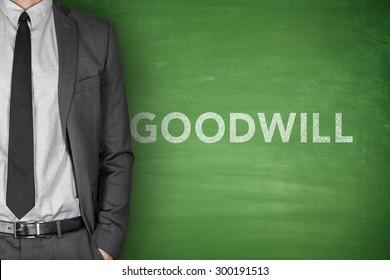 Goodwill text on green blackboard with businessman