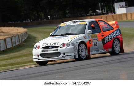 Goodwood, Chichester / UK - 5 July 2019: Ex Carlos Sainz 1997 Ford Escort Cosworth WRC with driver Nick Jarvis at the 2019 Goodwood Festival of Speed, Sussex, UK. The car takes the corner at speed.