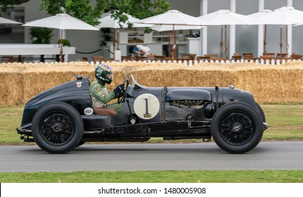 Goodwood, Chichester / UK - 5 July 2019: A dark green vintage 1936 Bentley race car, with 4.5 litre four cylinder engine, passes white umbrellas as it starts the hill climb at the Festival of Speed.