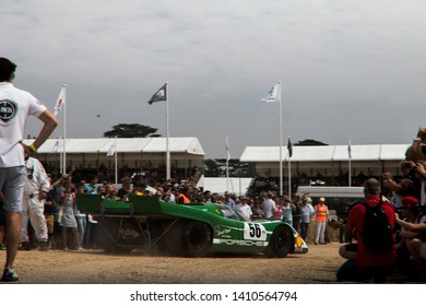 Goodwood, England - July 2018: classic Porsche 917 race car driving towards hill climb at an annual Goodwood Festival of Speed event. The car is surrounded by crowds of spectators at the event.