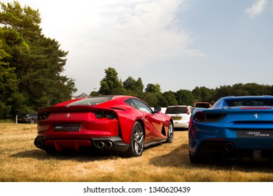 Goodwood, England - July 2018: Red Ferrari 812 Superfast supercar, parked next to a blue Ferrari 488 GTS, attending annual Goodwood Festival of Speed event in South England.