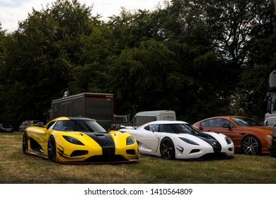 Goodwood, England - July 2018: two supercars by a Swedish brand Koenigsegg, yellow Agera RS and white Agera R, attending annual Goodwood Festival of Speed event.
