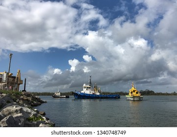 Goodwood Island, NSW / Australia - March 4 2019: Three tugboats of different size - 'Fury' the largest - preparing to depart Goodwood Island wharf, after docking a big recovery vessel for maintenance.