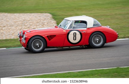 Goodwood, Sussex / UK - 13 Sept 2019: Car number 8, a red vintage convertible Austin Healey 3000 sports car races around the circuit during the Goodwood Revival. Red with white canvas roof.