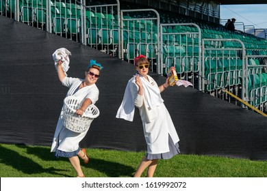 Goodwood, Sussex / UK - 15 September 2019: Two laughing ladies in vintage domestic aprons, headscarves and retro glasses dance with a laundry basket, packet of Daz detergent powder and a cigarette.