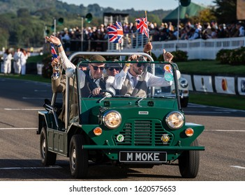 Goodwood, Sussex / UK - 15 September 2019: A classic  Austin Mini Moke takes part in the 60th anniversary parade at Revival. Four men in vintage costumes wave union jack flags from the open top.
