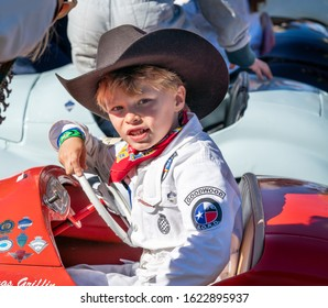 Goodwood, Sussex / UK - 15 September 2019: Smiling young driver, Briggs Griffin, sits behind the wheel of his red Austin J40 pedal car preparing to race in the Settrington Cup. He wears a cowboy hat.