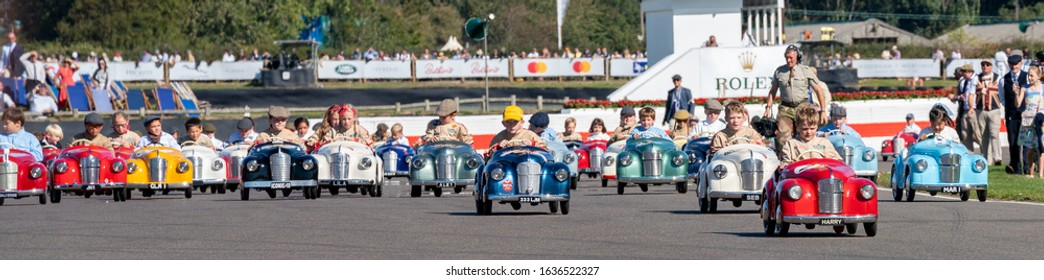 Goodwood, Sussex / UK - 15 September 2019: A panoramic wide view of kids in their colourful Austin J40 pedal cars: Settrington Cup, Revival. Harry Dark (no. 2) leads the field to win in his red car