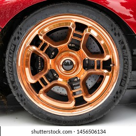 Goodwood, Sussex / UK - 7 July 2019: Classy gold wheel with five spokes set against red bodywork symbolises the latest De Tomaso P72. Costing more than £600,000 and debuting at the Festival of Speed.