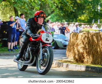 Goodwood, Sussex, UK - 9 July 2021: Eighty-seven year old (87) Sammy Miller rides his 1957 Gilera 500 Quattro motorcycle out of the paddock at the Festival of Speed to compete in the timed Hill Climb.