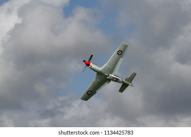 GOODWOOD, UK - SEPTEMBER 15, 2015: shot from below against mixed cloudy sky at the Battle of Britain commemoration, a Mustang P-51D in flight in sunshine.