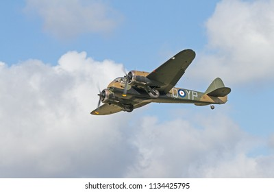 GOODWOOD, UK - SEPTEMBER 15, 2015: Shot to the side from below at the battle of Britain commemoration, against mixed broken clouds, a Bristol Blenheim aircraft flying in sunshine.