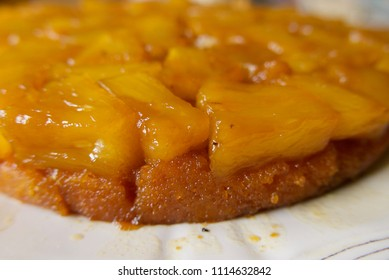 Gooey caramelized edge of a pineapple upside down cake seen up close, on a white plate.