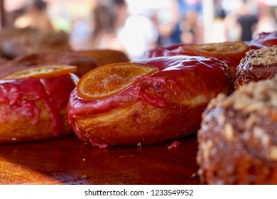 Gooey donuts on display with pink frosting & candied orange. Sitting in the shade, on display for sale outdoors.