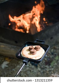 Gooey melted chocolate candies sit on top of a pancake in a pie iron with a lively campfire in the background. Photo taken in southern Wisconsin.