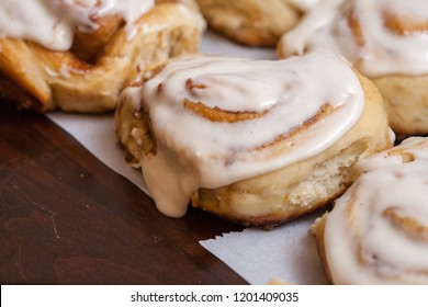 Gooey oozing cinnamon rolls sitting on table.