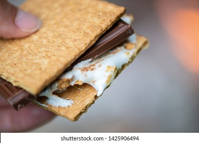 A gooey s'more by a camp fire.
