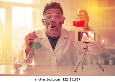 Goofy blogger overreacting. Goofy blogger overreacting on camera at his studio creating video about chemistry and experiments