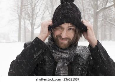 Goofy guy adjusting black winter hat during a snow storm.