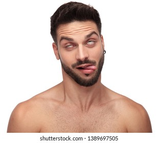 goofy naked man fooling around rolling his eyes and exposing his tongue on white background