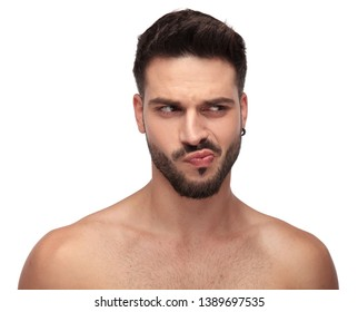 goofy undressed guy with beard looking away curious on white background