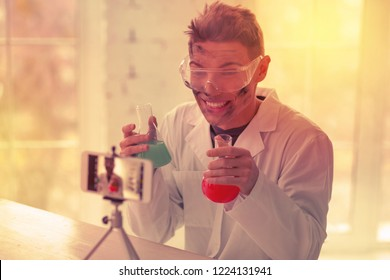 Goofy vlogger. Goofy vlogger streaming his tutorial going wrong holding two flasks with reagents
