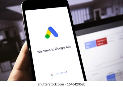 Google Ads app on the screen smartphone with notebook in the dark closeup. Ads is a service of contextual, basically, search advertising from Google. Moscow, Russia - October 21, 2019