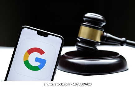 Google logo seen on the smartphone placed next to the judges gavel. Concept for a lawsuit, legal case, antitrust and fine. Real photo, not a montage. Stafford, United Kingdom - December 15 2020: