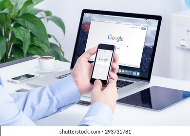 Google search on Apple iPhone screen and Macbook Pro Retina display that is on office desk. Multi devices multitasking concept. All gadgets in full focus. Varna, Bulgaria - May 29, 2015.