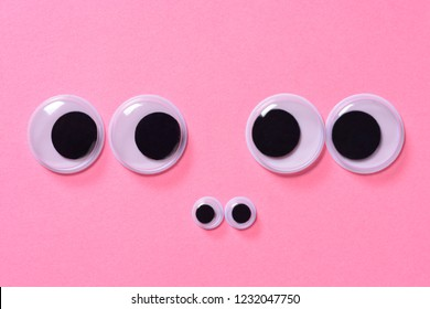 Googly eyes of family of two people with child on rose background. Close up.
